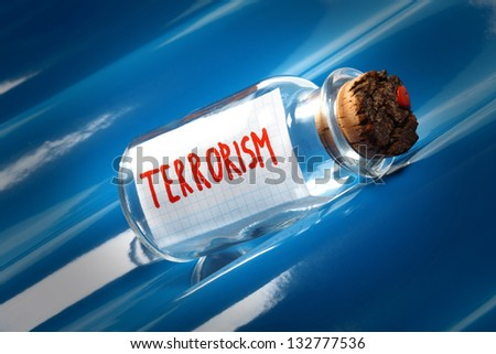 "An artistic concept of a vintage bottle with a message ""Terrorism"" floating on blue waves - stock photo"