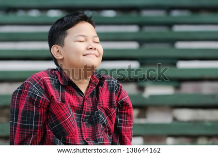an asian boy smiling with eyes closed shows a happiness expression