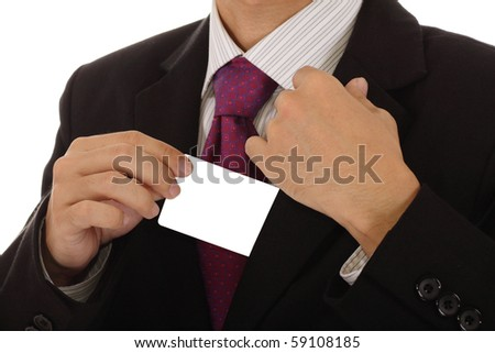 An Asian businessman pulling a card out of his coat. Clipping path included for the card. - stock photo
