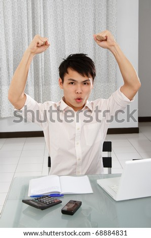 An Asian college student raising arms in triumph - stock photo