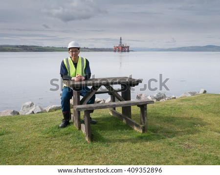 An asian engineer sitting on the desk in front of semi submersible oil rig - stock photo