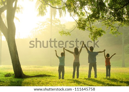 an asian family jumping in joy in the park during a beautiful sunrise, backlight