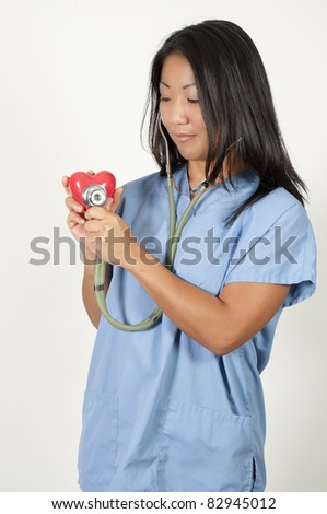 An Asian female cardiologist holding a red heart - stock photo
