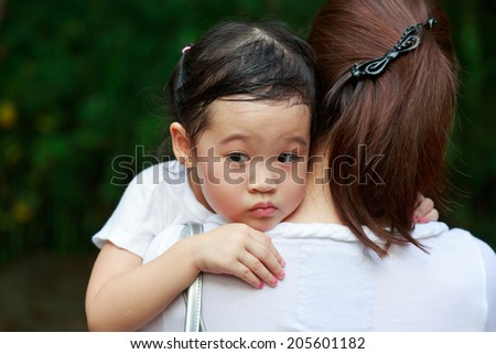 An Asian girl hugs her mother worrying about her scary surrounding