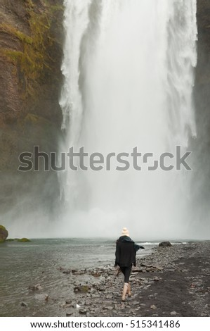 An Asian girl wearing a woolly hat and wellington boots walks beside a river and over rocks towards the Seljalandsfoss waterfall in  Iceland.