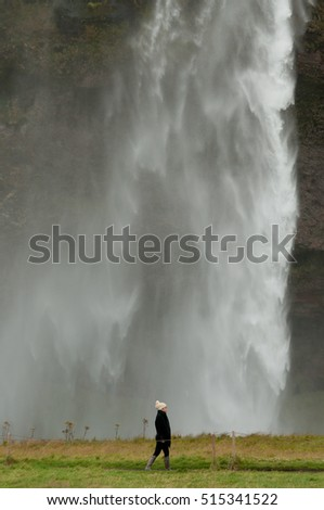 An Asian girl wearing a woolly hat and wellington boots walks by the magnificent Seljalandsfoss waterfall in Iceland, which makes her look tiny in comparison.