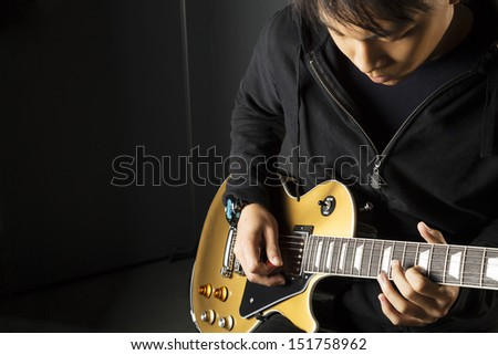 An Asian guitarist playing electric guitar with copy space on the left. - stock photo