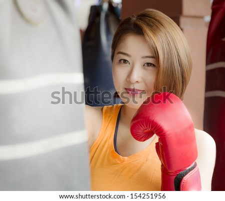 An Asian lady waring red glove practicing boxing. - stock photo