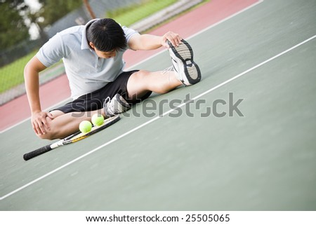 An asian male tennis player stretches before playing