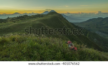 An Asian man crouches  while taking a photo on a mountain.