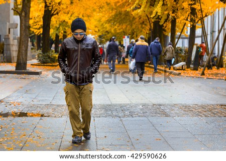 An Asian Man in a Brown Jacket Strolls in a Park in Autumn