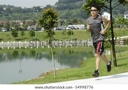 An Asian man jogging at a public park - stock photo