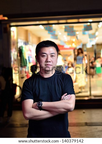 An Asian man standing in front of the shop Windows
