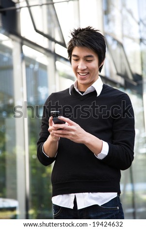 An asian man texting on the cellphone - stock photo