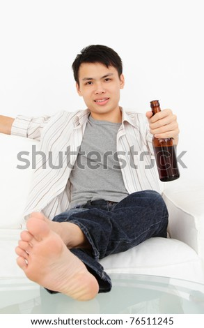 An Asian man watching TV with a bottle of beer - stock photo