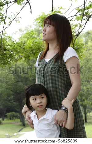 An Asian mother and her daughter at a park