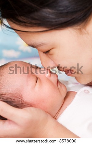 An asian mother kissing her sleeping baby boy - stock photo