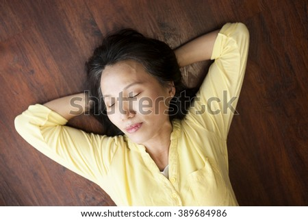 An Asian woman appears to be taking a brief nap on the floor.