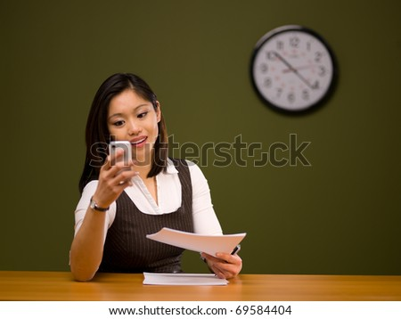 An asian woman paying bills online using a smartphone - stock photo