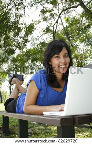 An Asian woman using her laptop on a park bench