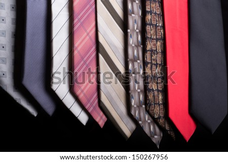 An assortment of different colorful neckties each with a different style and pattern - stock photo