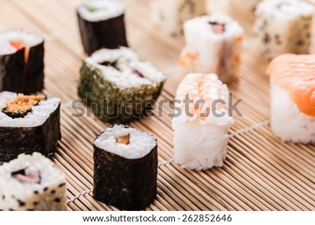 an assortment of different sushi pieces on a wooden bamboo sushi mat in a japanese restaurant - stock photo