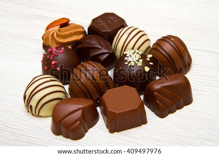 An assortment of fine chocolates in white, dark, and milk chocolate on white wood - stock photo