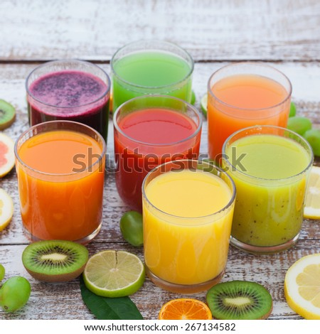 An assortment of fresh juices from fruits and vegetables. Glasses of tasty fresh juice, on wooden desk. Unusual top view - stock photo