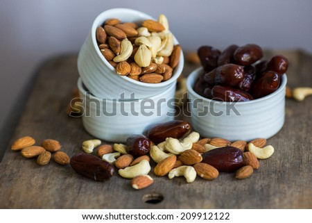 An assortment of healthy nuts in a bowl : almond, cashew, dates and hazelnut, making a healthy snack alternative - stock photo