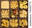 an assortment of italian pasta, nine different varieties separated in a decorative box - stock photo