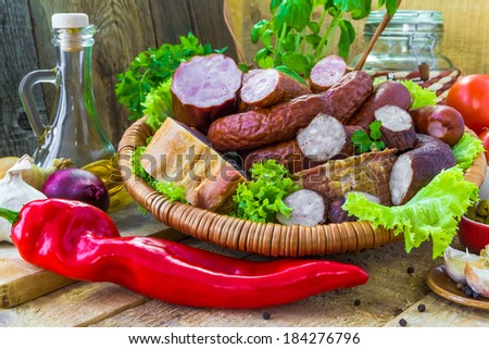 An assortment of meats - sausage and bacon with green