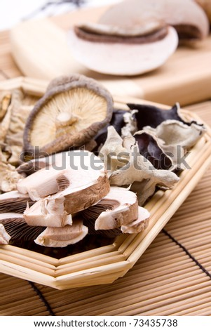 An assortment of mushrooms, including fresh portobellos, dried shitakes and dried woodears. - stock photo