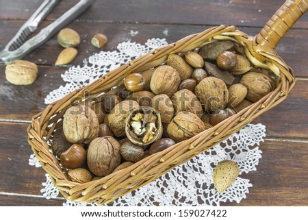 An assortment of nuts in a basket on wooden table - stock photo