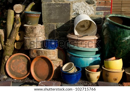 An assortment of plant pots of various shapes, colour and sizes stacked up in a garden amongst logs. - stock photo