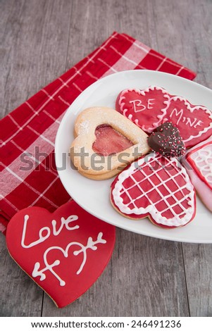 An assortment of pretty valentine cookies with a red napkin - stock photo