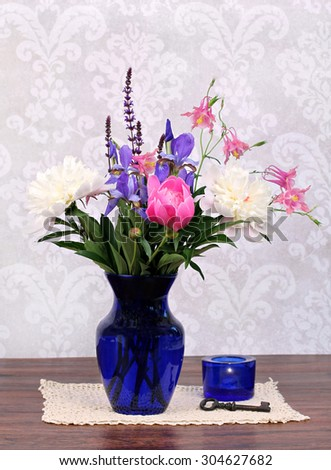 An assortment of typical and beautiful spring flowers in a navy vase with candle and antique key to the side.Arrangement on an antique doily. - stock photo