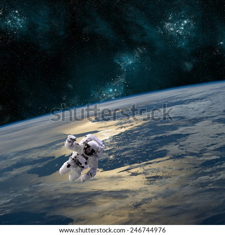 An astronaut floats above Earth. The planet sees the glow of the sun while a heaviiy cratered moon rises in front of a star filled sky. Elements of this Image Furnished by NASA.