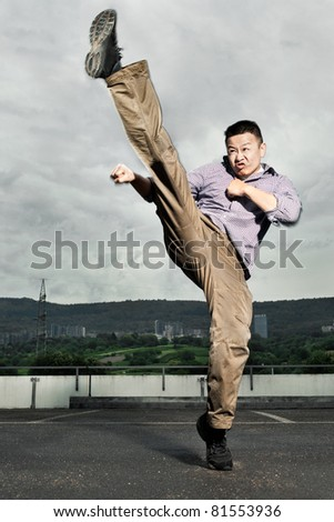 An athlete performing a powerful martial arts kick in a dramatic cloudscape with motion blur. - stock photo