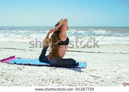 an athletic brown haired woman is doing yoga exercise on beach in Kapotasana or Pigeon Pose with foot in elbow  on an empty beach at the gulf of mexico in bonita springs florida with long hair bl - stock photo