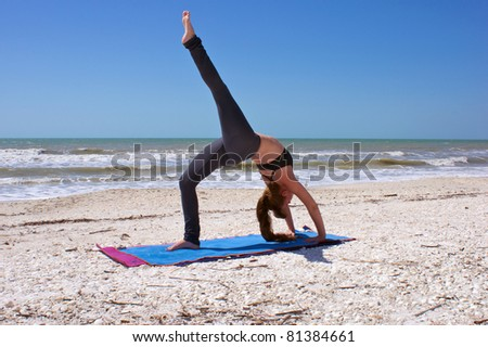 an athletic brown haired woman is doing yoga exercise one leg full wheel pose or Urdhva Dhanurasana also known as upward bow posture on an empty beach at the gulf of mexico in bonita springs florida - stock photo
