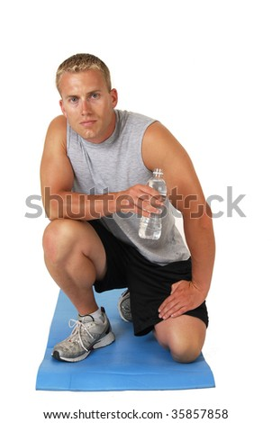 An athletic muscular man drinking water after a workout - stock photo