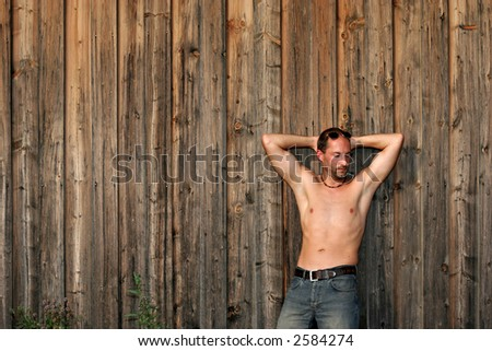 An athletic muscular young man in jeans leaning against a rustical wooden wall. - stock photo