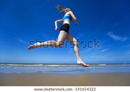 An athletic runner jogging along a sandy beach at the oceans edge.