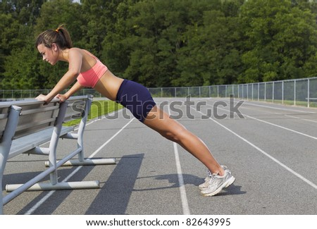 An athletic teenager stretching before exercising on a track outdoors - stock photo