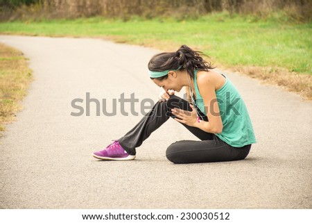 An athletic woman holds her knee in pain while sitting on a running path outside.  - stock photo