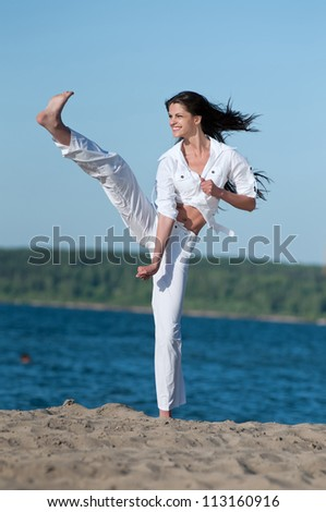 An athletic woman performing a kick in an sand beach - stock photo