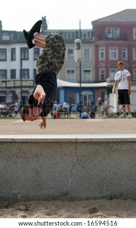"An athletic young Briton engages in his passion for ""parkour"" or ""free running"" on the seafront at Great Yarmouth. The blurred figure on the right is also model released. - stock photo"