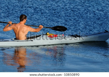 An athletic young male kayaker with bare upper body is paddling off into calm blue waters of Mission Bay, San Diego, California.