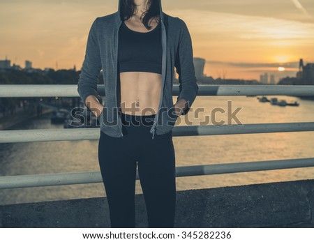 An athletic young woman with toned abs is standing on a bridge in London at sunrise - stock photo