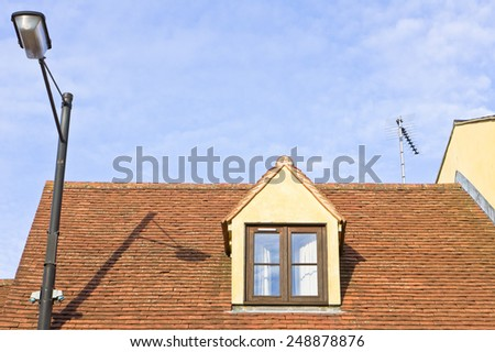 An attic room window in the roof of a house - stock photo